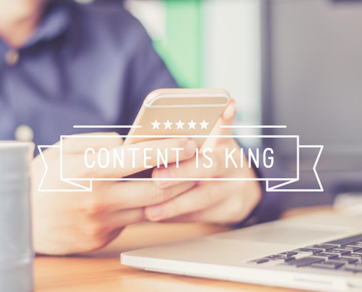 אדם מחזיק טלפון וברקע רשום תוכן הוא המלך - כתיבת תכנים